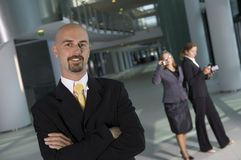 Business man smiling. Business man standing in front of two business women Royalty Free Stock Image
