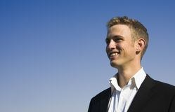 Business man smiling. Young business man smiling under clear blue sky stock photography