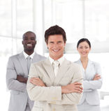 Business man smiling in front of Business team. Young Business man smiling in front of an arms folded Business team Stock Photography