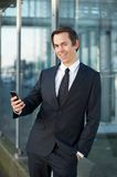 Business man smiling outdoors with cellphone Stock Photography