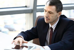 Business man smiling while working on tablet Stock Photography