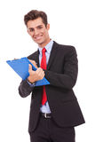 Business man smiling and writing on clipboard Stock Photography