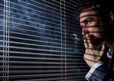 Business man smokes. At the window blinds Stock Image