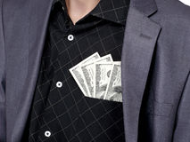 Business man with some dollars. Business man standing with some american dollars in his shirt pocket, close up Royalty Free Stock Images