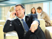 Business man speaking. On the cell phone while in a meeting Stock Photo