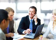 Business man speaking. On the phone while in a meeting Stock Photography