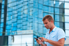 Business man speaking on phone in front of modern business building Royalty Free Stock Photo