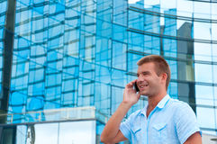 Business man speaking on phone in front of modern business building Royalty Free Stock Photography
