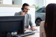 Business man speaking on the phone while in a meeting. Young business men speaking on the phone while in a meeting stock images