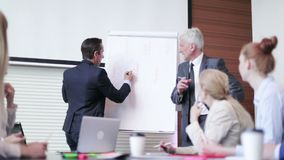 Business man speaking on seminar. Writing on whiteboard or flipchart stock footage