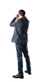Business man and spying binocular acting isolated white background Royalty Free Stock Images