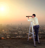 Business man spying lens on high building roof  against skyscrap Royalty Free Stock Photos