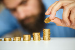 Business man stacking gold coins into increasing columns Stock Image