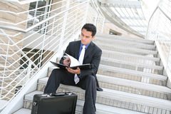 Business Man on Stairs Reviewing Notes Royalty Free Stock Image