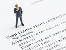 Business man stand on financial statement. Miniature business man stand on financial statement Royalty Free Stock Photography