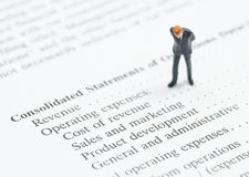 Business man stand on financial statement Royalty Free Stock Image
