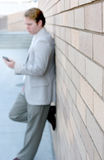 Business man standing. Against the wall with one leg up on the bricks Royalty Free Stock Photo