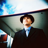 Business man standing. Under a blue sky with a black hat. Taken with a holga. (scanned from film Stock Photos