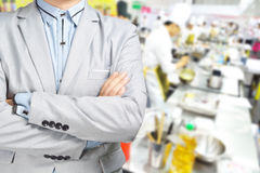 Business Man standing against the Background of Kitchen Stock Photo