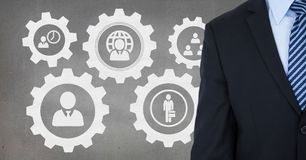 Business man standing against people in cogs graphics against grey background. Digital composite of Business man standing against people in cogs graphics against Stock Image
