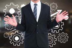 Business man standing against people in cogs graphics against office background Royalty Free Stock Images