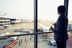 Business man is standing in airport and looking at aircraft flight through window Stock Image