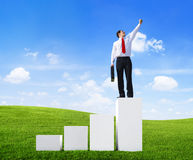 Business Man Standing on a Bar Graph with Arms Raised.  Stock Photos
