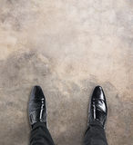 Business man standing at the beginning of a journey looking down at his feet. With copy space for a message Royalty Free Stock Images