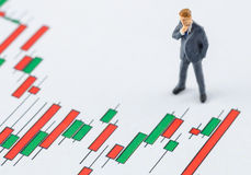 Business man standing on the candlestick stock chart. Miniature business man standing on the candlestick stock chart royalty free stock image