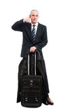 Business man standing with carry on luggage showing calling gest Stock Photography