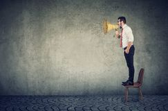 Business man standing on a chair and screaming into a megaphone royalty free stock images