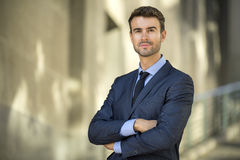 Business man standing confident with smile portrait. A successful business man in a suit standing smiling proud and confident for a portrait outdoors