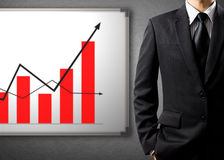 Business man standing and drawing growth chart on white board. Success concept Stock Photos