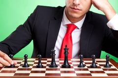 Business man standing in front of chess line-up Royalty Free Stock Photos