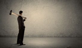 Business man standing in front of a grungy wall with a hammer Royalty Free Stock Photos
