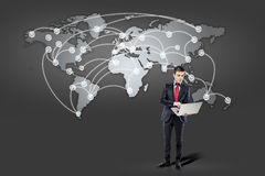 Business man standing in front of world map Stock Images