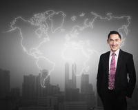 Business man standing in front of world map Royalty Free Stock Photo