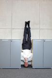 Business man standing on his head between cabinets in office Royalty Free Stock Photos