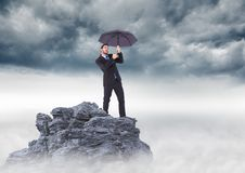 Business man standing on mountain peak with umbrella against stormy clouds Royalty Free Stock Photography