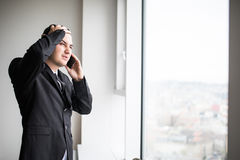 Business man standing next to large windows of his top floor office, looking at the view of the city while take bad news from his Royalty Free Stock Photos