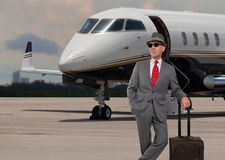 Business man standing next to a private jet Stock Image