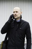Business man standing outdoor talking in telephone. Royalty Free Stock Image