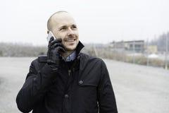 Business man standing outdoor talking in telephone. Swedish caucasian businessman. European Scandinavian. Smiling standing outdoor talking into telephone Stock Images