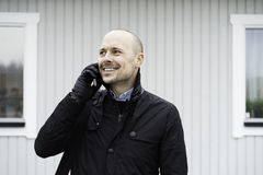 Business man standing outdoor talking in telephone. Swedish caucasian businessman. European Scandinavian. Standing outdoor smiling talking into telephone Royalty Free Stock Photography