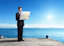 Business man standing on pier with map Stock Images
