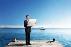 Business man standing on pier with map Royalty Free Stock Image