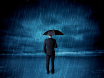 Business man standing in rain with an umbrella Stock Photography