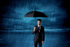 Business man standing in rain with an umbrella Stock Images