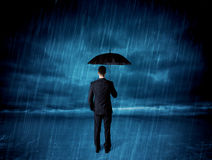 Business man standing in rain with an umbrella Royalty Free Stock Images