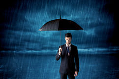 Business man standing in rain with an umbrella Stock Image